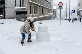 Una paseante hace un muñeco de nieve en la carrera de San Jerónimo