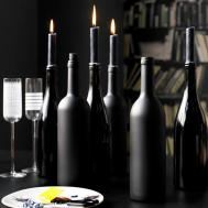 Assorted black spray painted bottles as dining table centrepiece with lit candles L etc 01/2008 Pub Orig