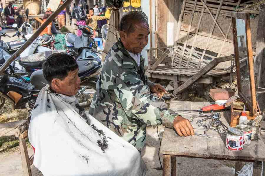 LE coiffeur officie sur le marché