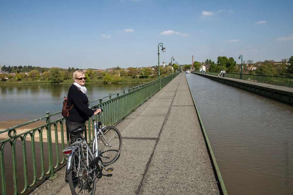 Mo avec son vélo à l'entrée du pont