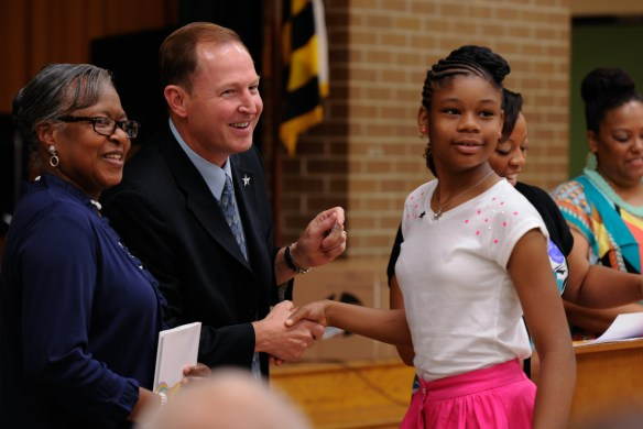 Young leader Anaya Jackson as she receives a silver star pin from John Rogers, Joint Base Andrews 844th Communications Group deputy director, at the Francis T. Evans Elementary School fifth grade graduation ceremony, Clinton, Md., June 12. (U.S. Air Force photo/Aimee Fujikawa)