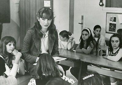 Une institutrice est assise sur une table parmi ses élèves.