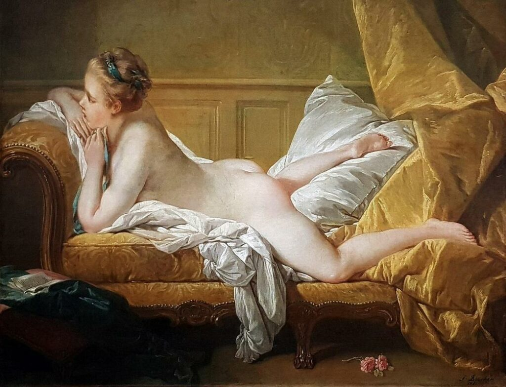 Une femme nue est allongée sur le ventre sur un sofa.