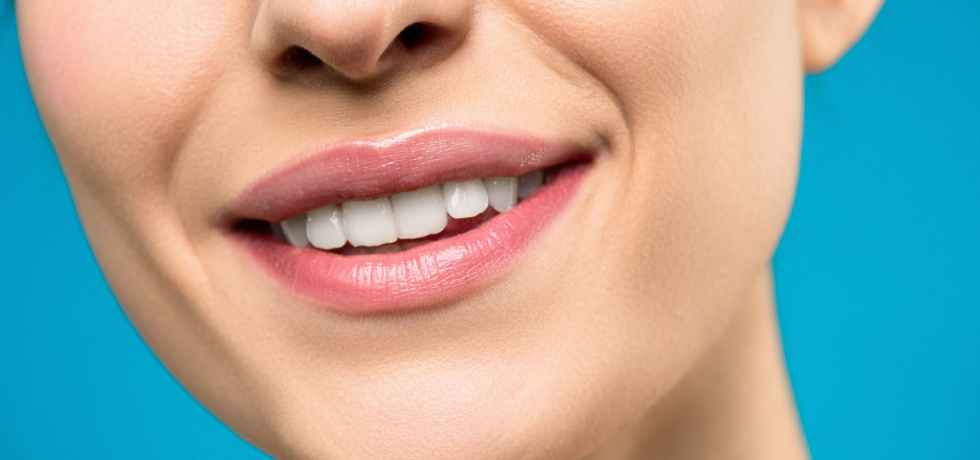 close up photo of woman with pink lipstick smiling