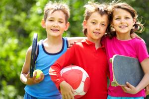 Drei Kinder mit Sportgeräten in der Hand.