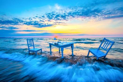 Meeresrauschen. Ein Bild aus der Ausstellung Strandgut. Blauer Tisch mit Stühlen in der Ostsee