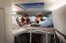 Wer sich für den Grand California 600 entscheidet, hat die Wahl zwischen einem großen Stauraum im neuen Camper-Hochdach oder dem dort optional integrierten Kinderbett (1,65 Meter Liegelänge) samt in diesem Fall ebenfalls eingebautem Panoramadach (700 x 850 mm) und damit freiem Blick in den Sternenhimmel. Foto: Volkswagen