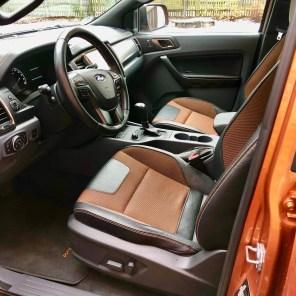 """Die Sitze mit gutem Seitenhalt sind in einem orangenen Farbton gehalten und an der Rücklehne mit einem auffallendem """"Wildtrak""""-Schriftzug verziert."""