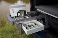 Die Miniküche besteht aus einem einflammigen Gaskocher inklusive Windschott sowie praktischen Ablagen und Stauräumen für Kochgerätschaften und Vorräte. © VWN