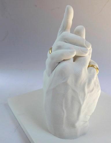 Foto des Gipsabdrucks zweier Hände mit vergoldeten Ringen
