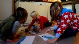 Foto mit Luis und Bela und einem weiteren Jungen beim Malen mit Wasserfarben.