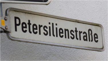 """Foto eines Straßennamenschildes, das die Aufschrift """"Petersilienstraße"""" zeigt."""
