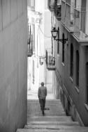 Foto einer engen, bergigen Gasse zwischen Häusern, auf der gerade ein Mann die Treppen hinunter geht.