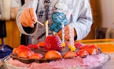 Foto von einem Geburtstagskuchen, auf dem gerade die Kerzen angezündet werden.