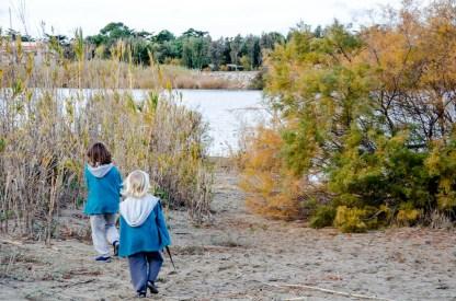 Foto von zwei Kindern, die gerade auf dem Weg zum Flußstrand sind.