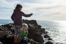 Foto von zwie Kindern auf einer Mole, die die Aussicht auf das Meer genießen.