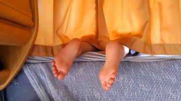 Foto von zwei Füßen, die unter dem Vorhang des Alkovens eines Wohnmobils heraussehen.