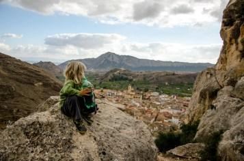 Foto von einem Kind, das auf einem Fels sitzt.