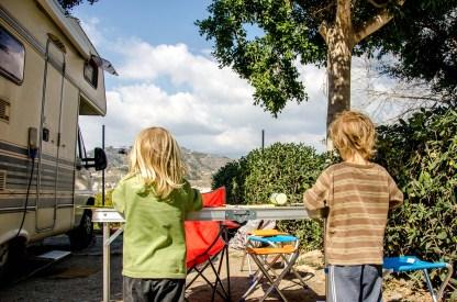 Foto von Kindern, die an einem Tisch vor dem Wohnmobil malen.