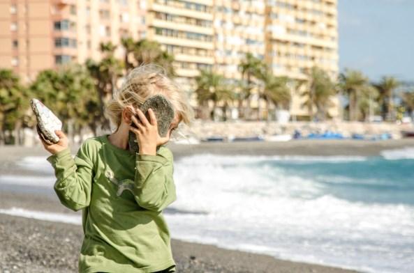 Foto eines Kindes, das am Strand Steine und Fliesen findet.