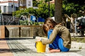 Foto von Kind, dass mit einem Eimer vor einen Springbrunnen hockt.