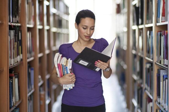 Eine Frau in einer Bibliothek. Sie liest in einem Ordner und hat viele Bücher auf dem Arm