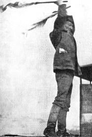 Baku, 1922: Komponist Arsenij Avraamov auf dem Dach eines Hauses, mit Flaggen Fabriksirenen und Dampfpfeifen dirigierend. Foto Wikimedia Commons
