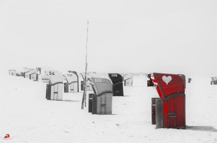 Roter Strandkorb auf schwarz-weißem Strand