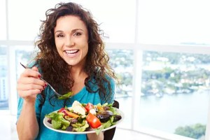 Beautiful happy female eating a salad
