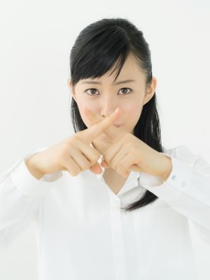 指でバツをしている女性
