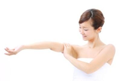 二の腕をマッサージする女性