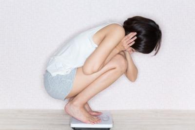 体重計に乗って悩んでいる女性