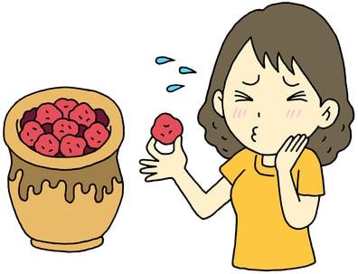 梅干しを食べて酸っぱい顔をする女性