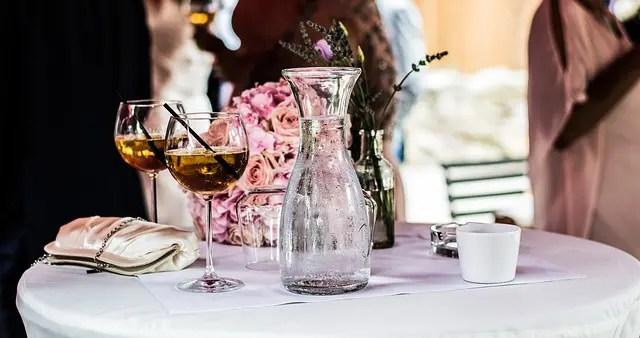 2 verre de vin rosé et une carafe d'eau fraiche sur une table entouré de femme