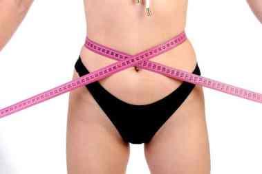 femme qui mesure la perte de poids sur ces hanches après son régime citron