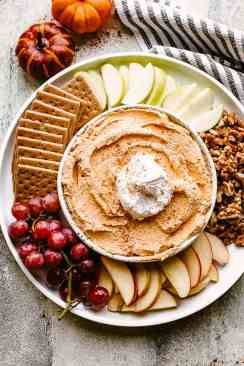 Pumpkin Fluff Dip served with apples, grapes, nuts, and cookies.