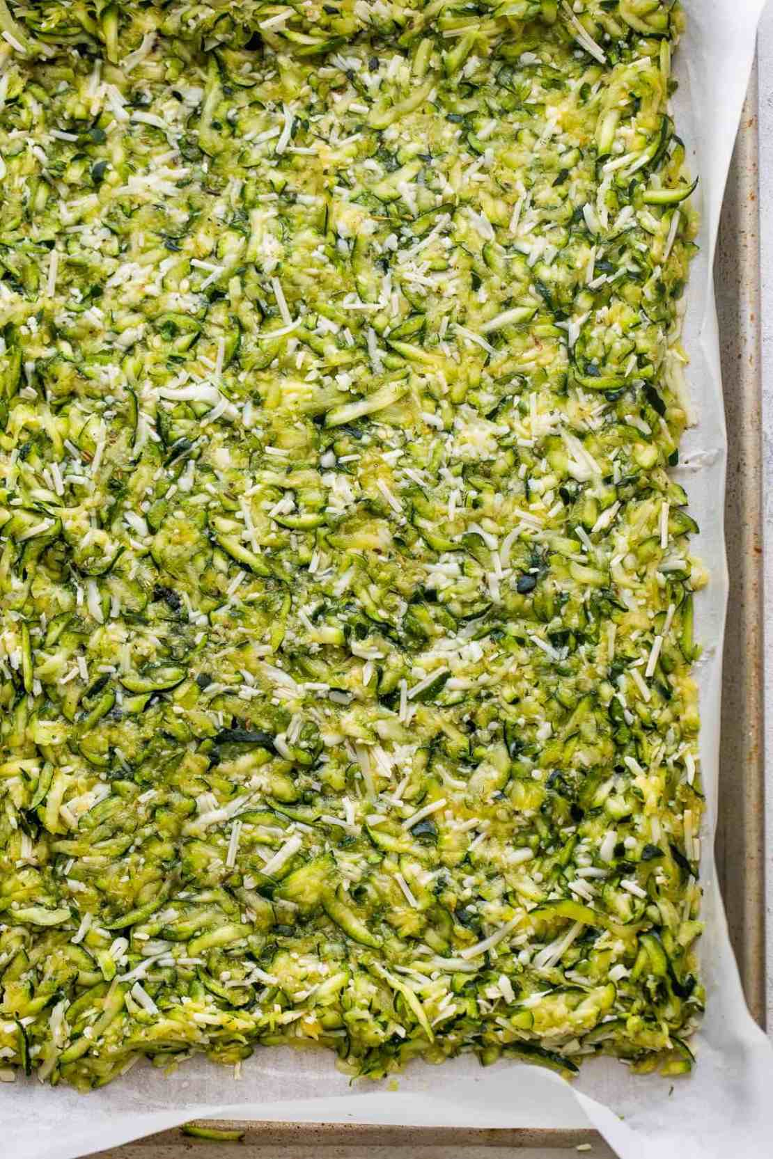 shredded zucchini and cheese mixture on the bottom of a baking dish lined with parchment paper