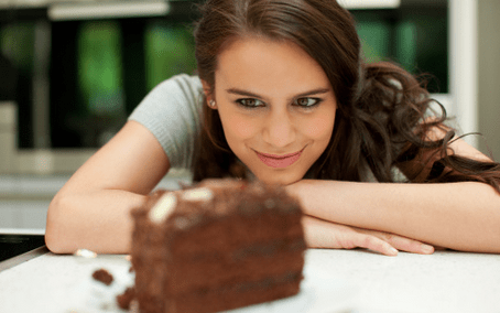 Young Woman looking at a piece of chocolate cake