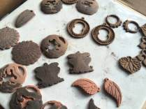 These are earring parts being fabricated from metal clay. There is a combination of bronze, copper, and steel here. Some parts are experiments in married-metal technique. After creation in one clay, the part is back-filled with a contrasting metal clay, then sanded and fired.