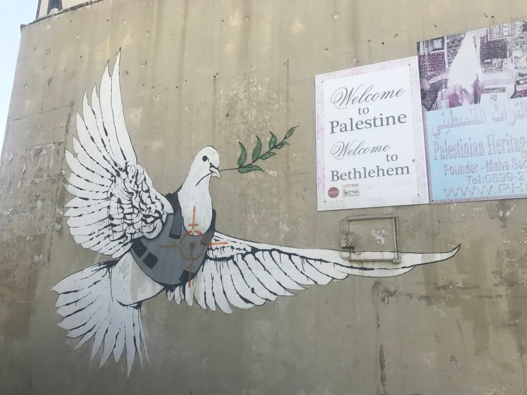 Graffiti wall art in Palestine of a dove of peace wearing a bullet proof vest by Banksy