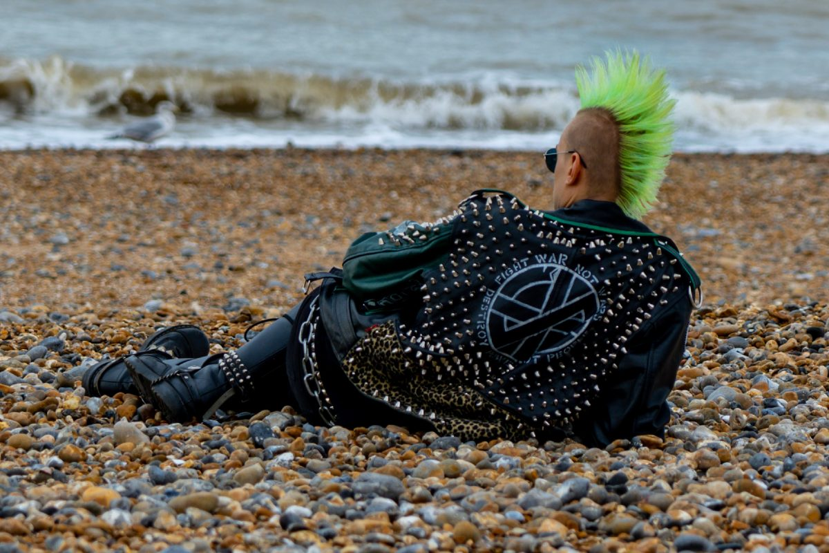 Punk rocker with green irokez/ mohawk hair style relaxes at the beach