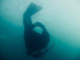 Un plongeur marche à l'envers avec ses palmes sur la glace