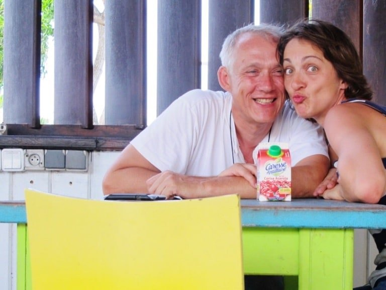 Un couple sourit en buvant un jus de fruit à l'aéroport en Martinique