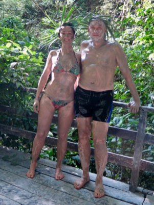 Un couple se tient dans la jungle couvert de boue avant de s'immerger dans des thermes naturelles
