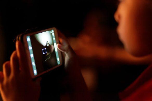 Un enfant joue à un jeu en ligne sur son smartphone.