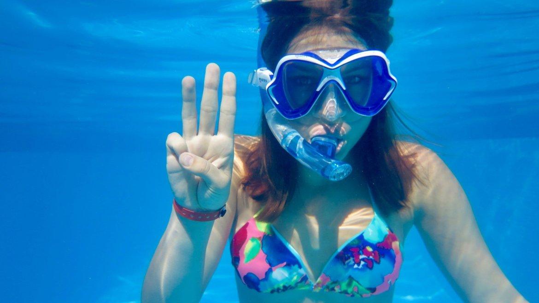 Une jeune fille montre un trois avec ses doigts pour expliquer le briefing de plongée