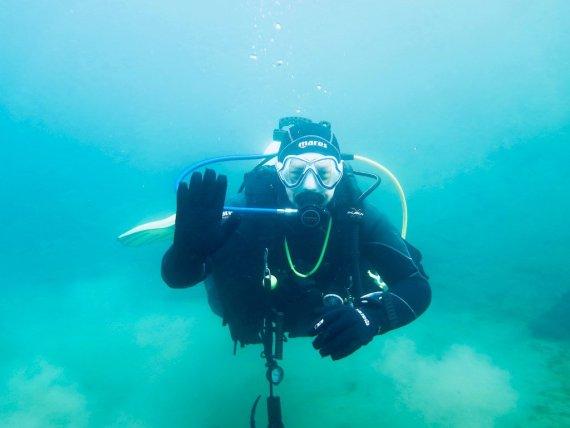 Un plongeur fait bonjour avec sa main