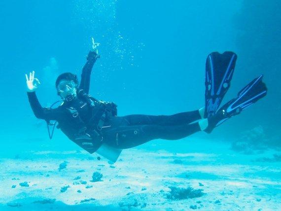 Une plongeuse fait le signe OK sous l'eau