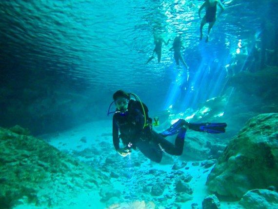 Une plongeuse s'immerge dans le cenote de Dos Ojos