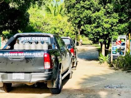 Des pick-up stationnent devant l'entrée du cenote de Chak Mool